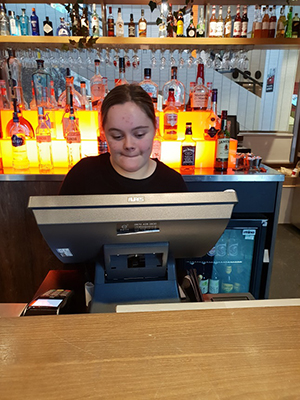Emily works on a cash register during her work placement.