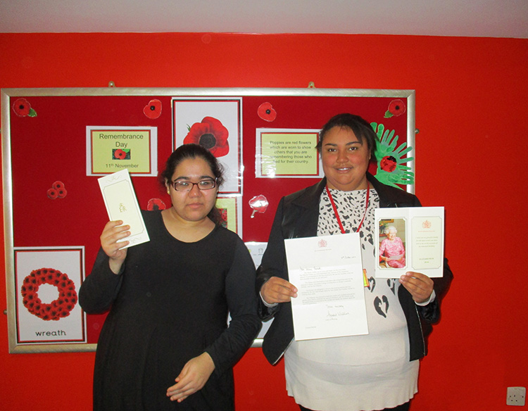 2 students holding Thank You cards from the Queen