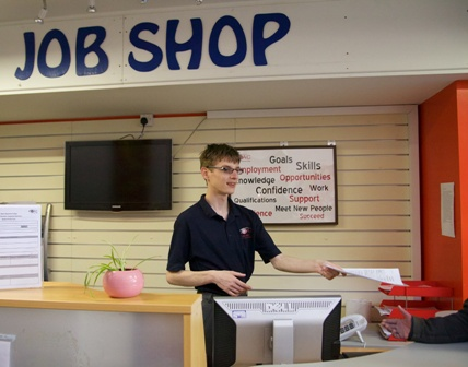 A student hands out a leaflet at the QAC Job Shop desk