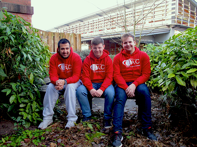 Student ambassadors Hamza, Will and Josh sitting on a bench with a leafy surrounding.