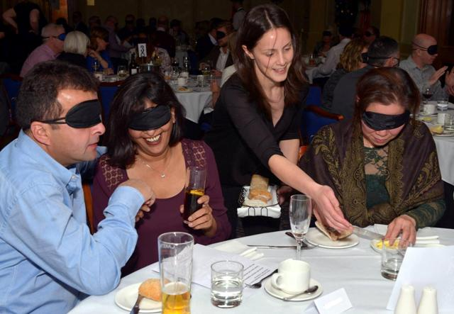 Waiting staff serve diners sat at a table wearing blindfolds