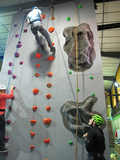2 students climbing a climbing wall with someone supervising at the bottom