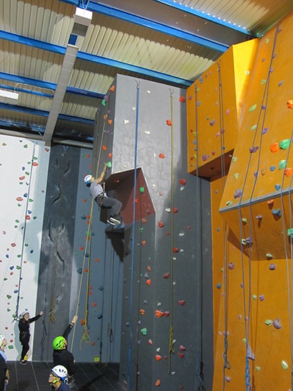 Student reaches the top of a climbing wall