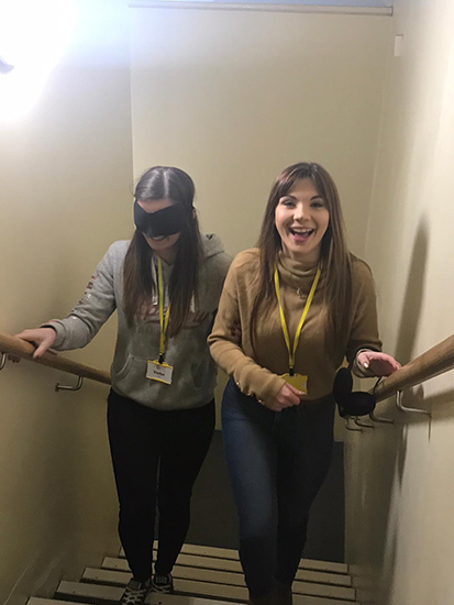 Two individuals going trough a sighted guide training taster, one sighted person leading the other who is blindfolded up a flight of stairs