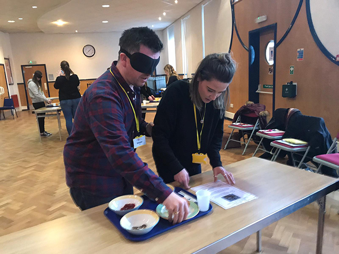 2 people involved in a blindfolded food preparation activity during the disability awareness day