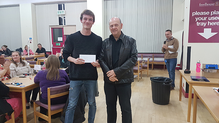Curry & Quiz Night winning team representative collecting prize from College principal Hugh Williams