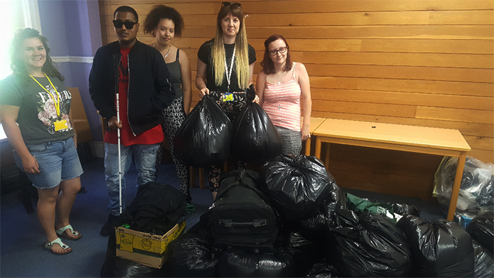 Students and staff pose for a photo with all of the collection bags the students amassed