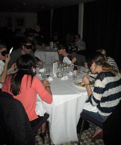 Diners sat wearing blindfolds eating around a table