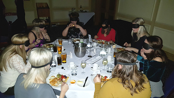 Group of blindfolded diners enjoying their meal at Dinner in the Dark