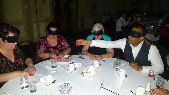 Group of people attempting to build a cat out of Play Doh whilst blindfolded
