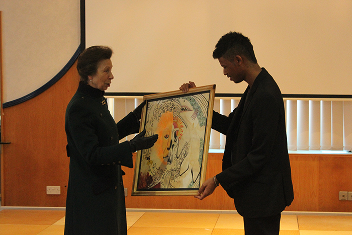 QAC student Konnor presenting HRH The Princess Royal with a painting created by him