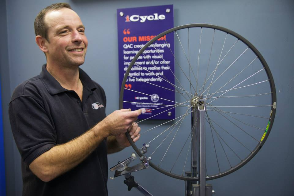 A member of the iCycle team repairs a bike wheel.