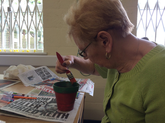 Lady decorating a plant pot during the workshop