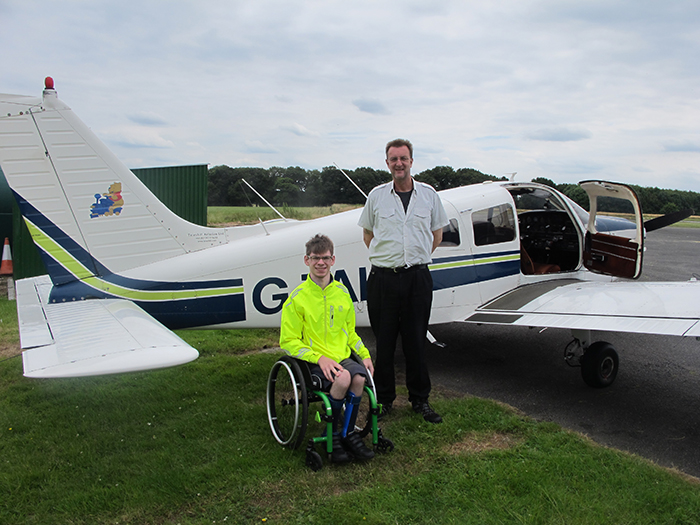 Bobby in wheelchair next to flight instructor, posing for photo in front of the plane