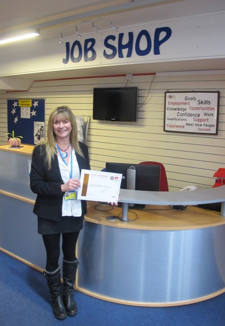 Fiona Bilsborough stands holding Bronze Standard accreditation award