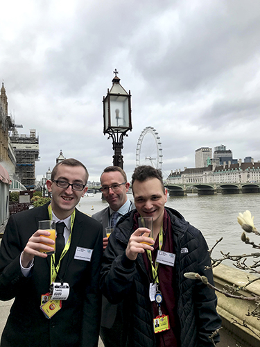 QAC Students Connor and Adam as well as Staff member Andy enjoying a drink outside the reception, with the London eye in the background