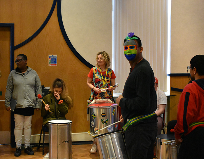 QAC students playing Samba music, one wearing a mask, during Mardi Gras celebrations