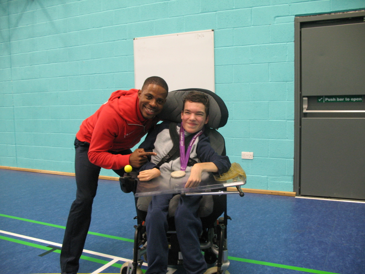 Mikail and QAC Student pose for photo with Mikail's Paralympic Silver Medal