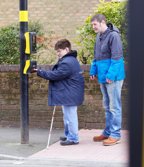 Mobility Officer and a young man using a long cane stand at a pedestrian crossing waiting to cross the road