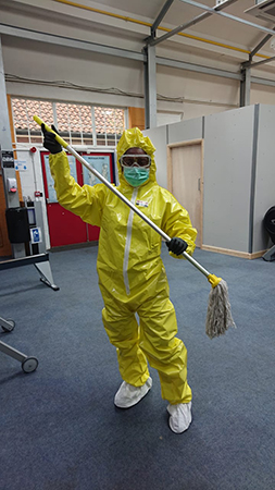An OCS cleaning worker wearing a yellow protective suit with goggles and a mask.