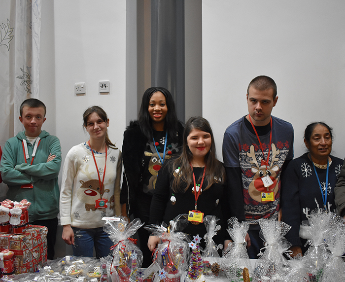 Students and staff pose for photo behind their stall at the Christmas Fayre