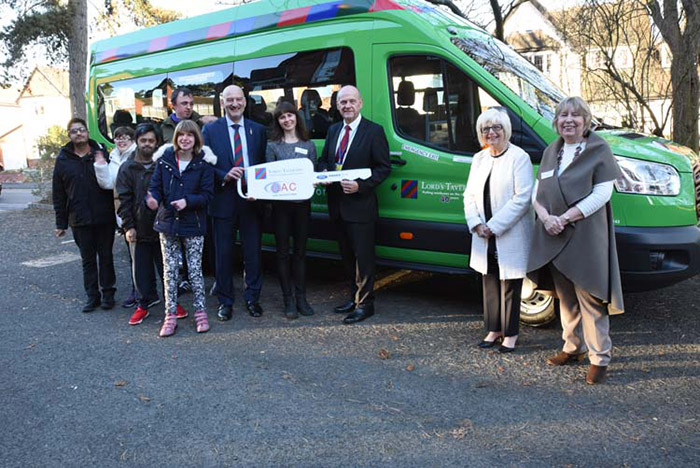 PFL Green and visitors with cardboard key in front of the minibus