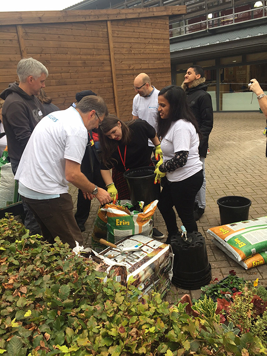 QAC Students and Barclays staff filling buckets with compost