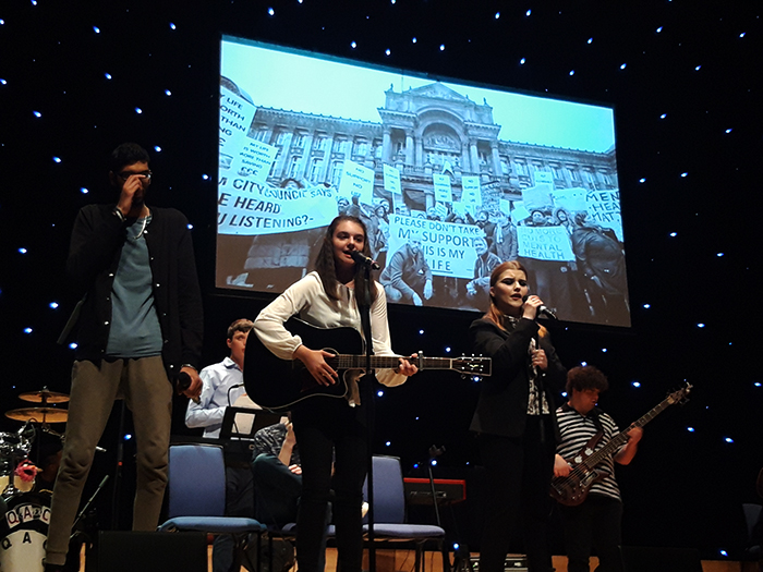Members of the QAC Collective perform one of their chosen songs on stage at the Birmingham Town Hall