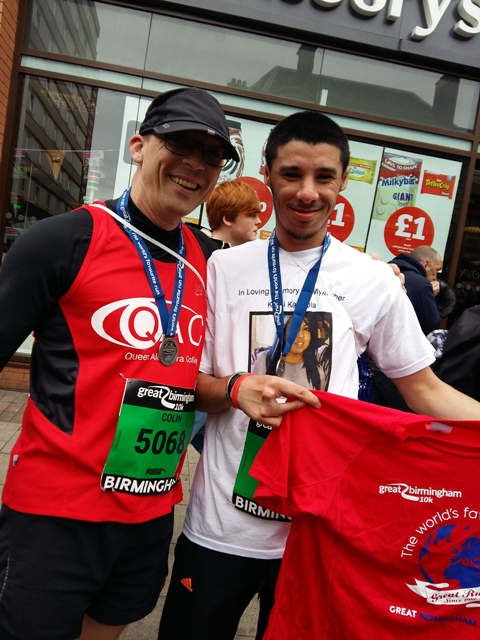 QAC student, Sanjay, proudly shows off his t-shirt and medal at the finish line alongside a QAC member of staff