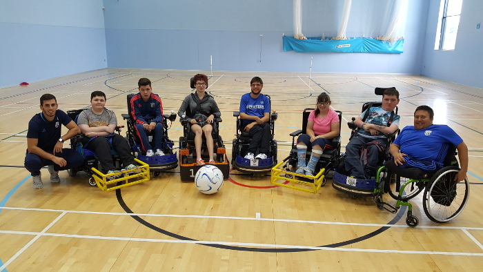 QAC students and WBA coaches posing for a photo during Powerchair Football training