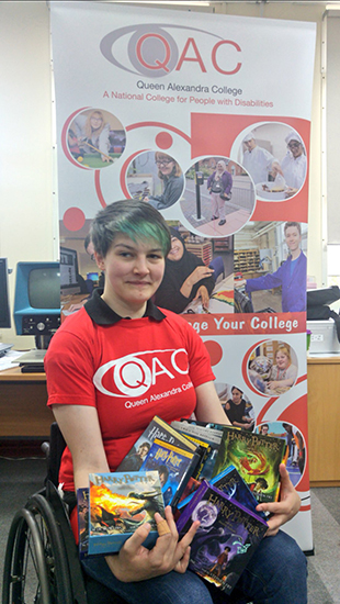 QAC Student Ruth holding up some of the items donated by J.K. Rowling