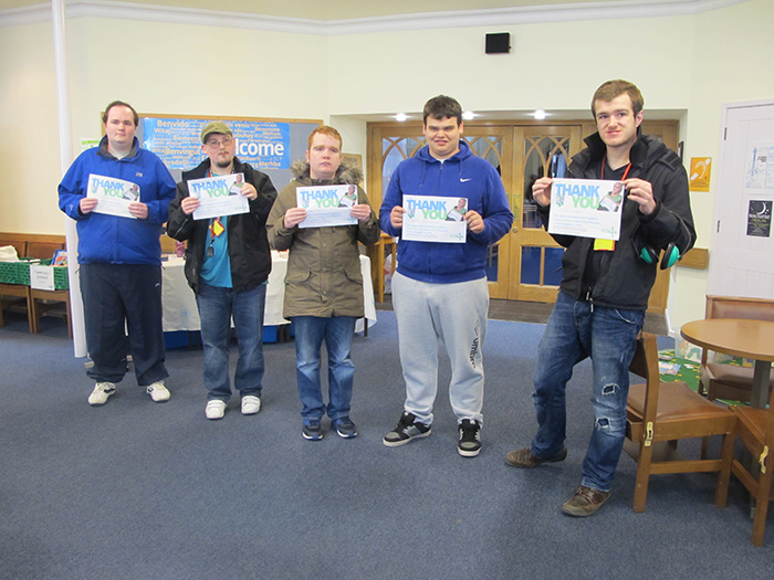 Students holding certificates following donation