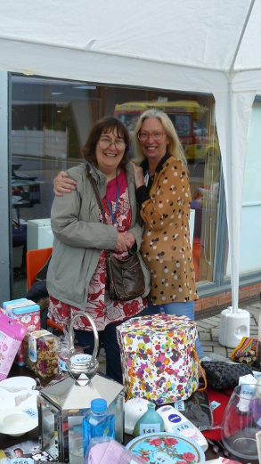 Two ladies behind a stall at the QAC Summer Fete, posing for a photo