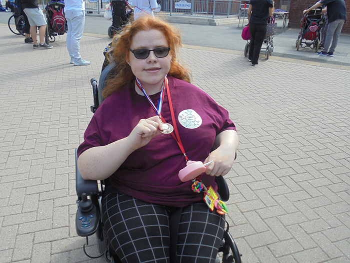 A student posing for a photo to show off her medal received during the Summer Games