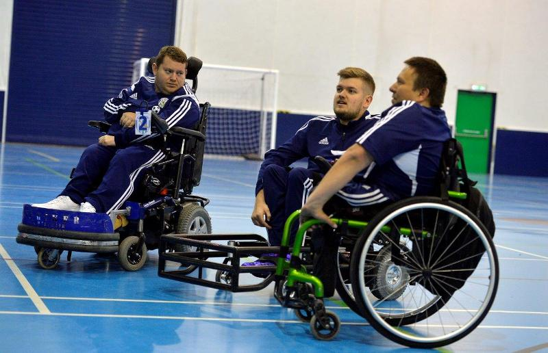 Three powerchair football players chat to each other in sports hall