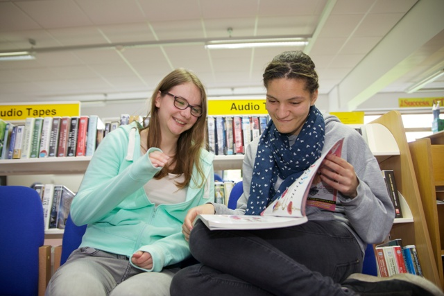 Two female students smile while looking at a book in the library