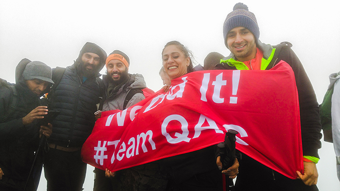 Inspire2binspired team with the #TeamQAC flag at the summit of Mount Snowdon