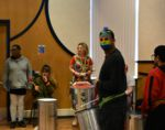 QAC Student in a Mardi Gras mask playing drum