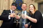 Event organisers hold a glass of Champagne