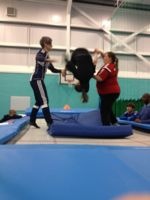 Student and instructors stand on trampoline