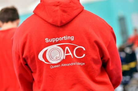 A person wears a red QAC hoodie with 'Supporting QAC' written on the back