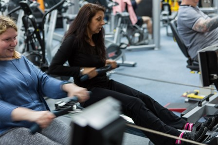 Independence Plus client and supporting staff member use the rowing machines
