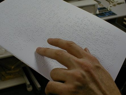 A close up of a person's hand reading braille