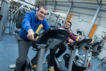 Two QAC students use the exercise bikes