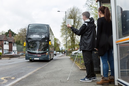 QAC student waits at a bus stop with a Rehabilitation and Travel Training Officer supporting