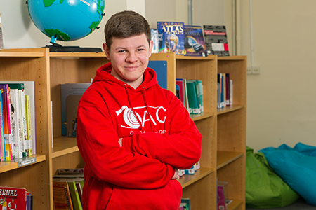 QAC Student Will poses for a photo in the College library